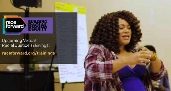 Person with long curly hair gesturing in training environment. Text: Race Forward, Building Racial Equity. Upcoming Virtual Racial Justice Trainings.
