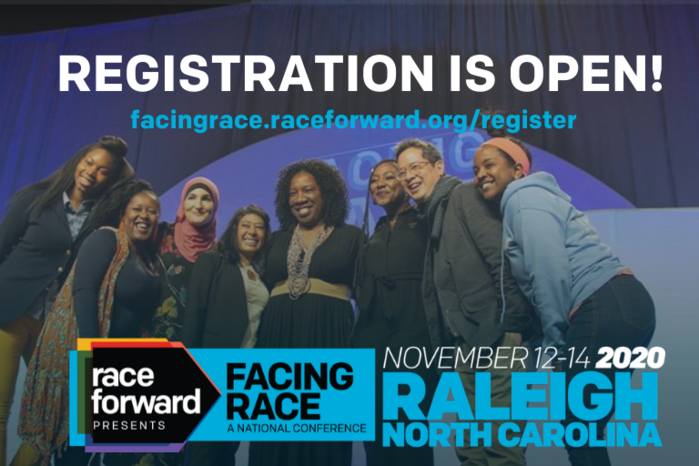 photo of a multiracial group on stage at facing race 2018 with Tarana Burke, smiling