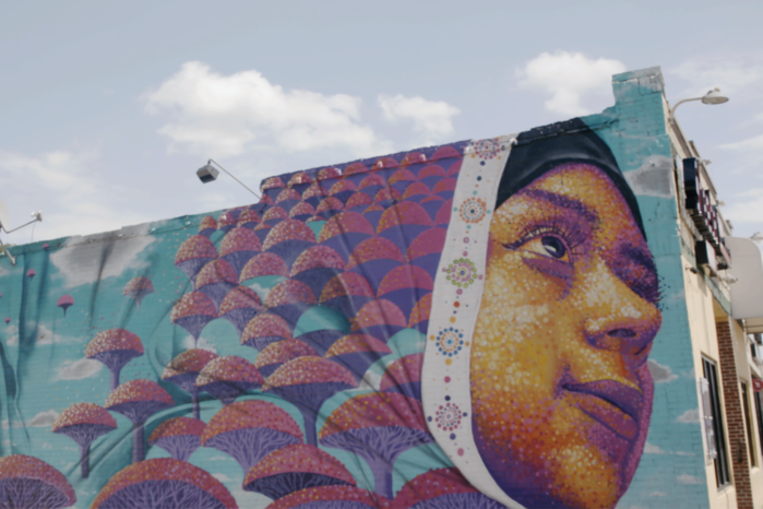 Mural of girls with colorful head coverings on side of building in Detroit