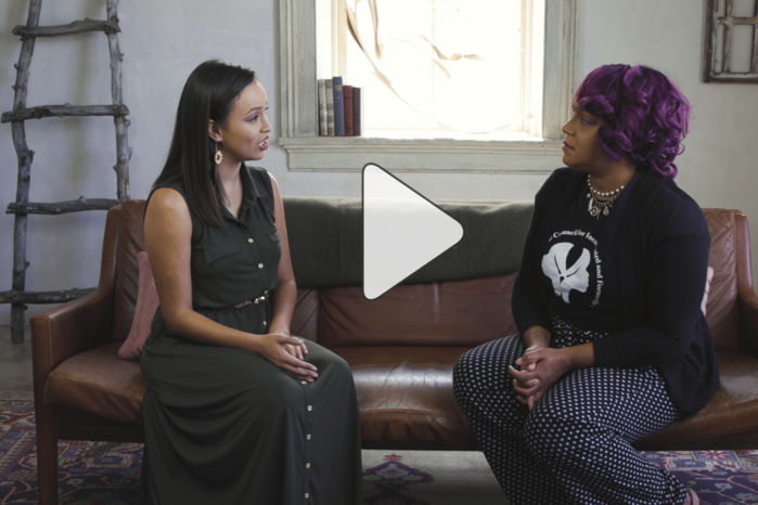 two women of color facing each other on a couch talking