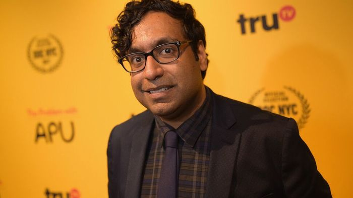 Hari Kondabolu wearing a dark plaid shirt, glasses, and a black jacket and tie.